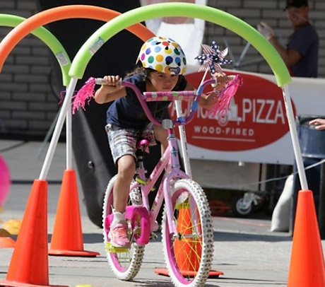 kid riding bike through obstacle course