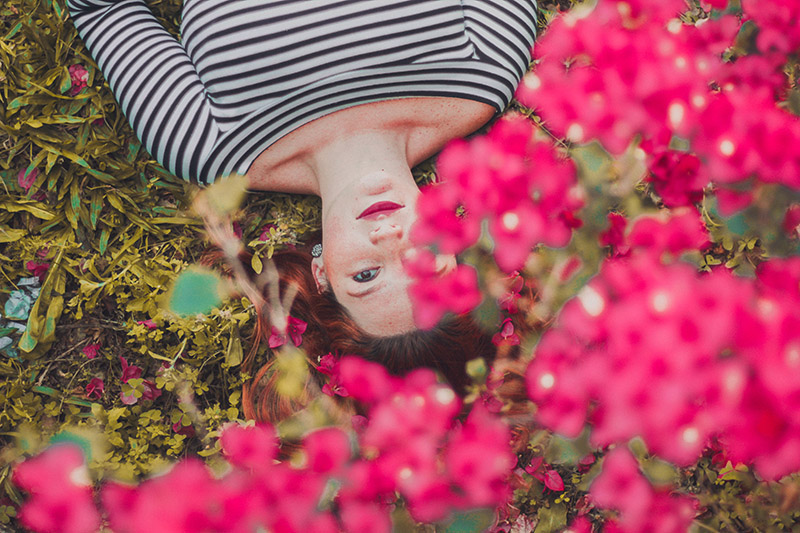 woman laying under flowers